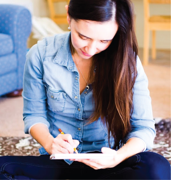 Artist, illustrator and surface pattern designer Oksancia is sitting on the floor and drawing in her sketchbook